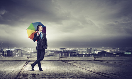rainbow umbrella: Young handsome businessman in suit with colorful umbrella Stock Photo