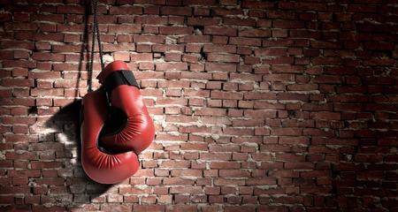 壁に掛かっている赤いボクシング グローブのペア