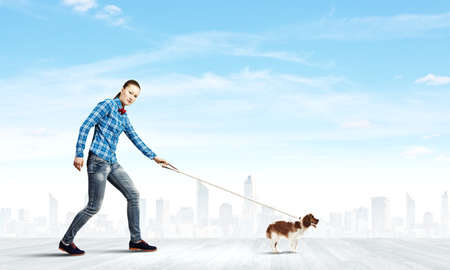 Young woman in casual holding dog on lead photo
