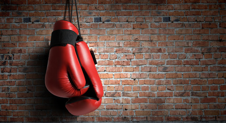 boxing sport: Pair of red boxing gloves hanging on wall