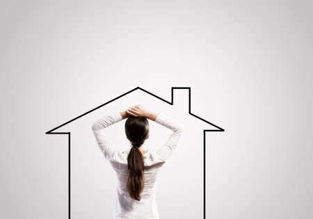 Rear view of thoughtful woman looking at house figure photo