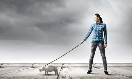 positivism: Young woman in casual holding rhino on lead