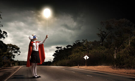 Cute girl of school age in superhero costume with balloon in hand photo