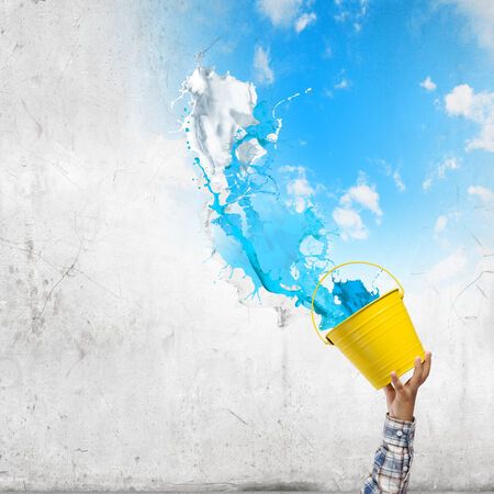 express feelings: Close up of hand splashing colorful paint from bucket