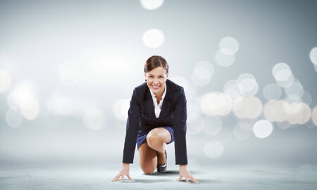 Young attractive businesswoman standing in start position photo