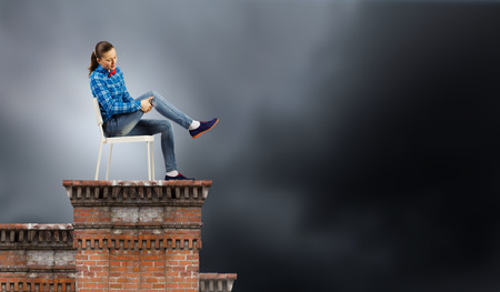 Young woman in shirt sitting in chair on building roof photo