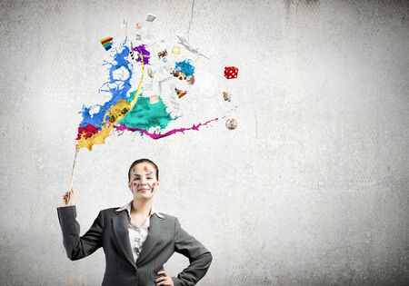 Young attractive businesswoman with paint brush in hand photo