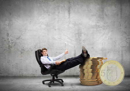 Young confident businessman sitting in chair with legs on stack of coins photo