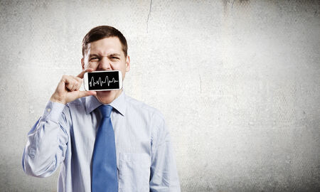 Young handsome businessman hiding mouth behind mobile phone photo