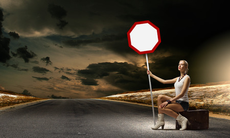 Young woman sitting on suitcase and holding roadsign photo