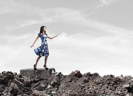 Young woman in blue dress walking among city ruins photo
