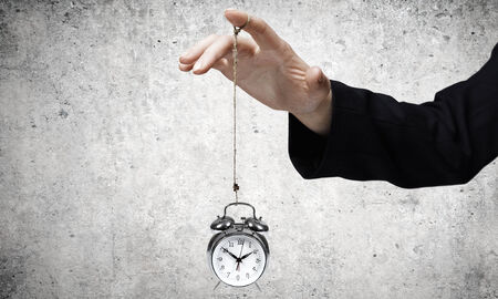 Close up of businessman holding clock on rope photo