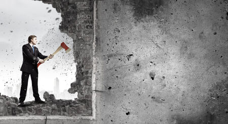 determinism: Young determined businessman crashing wall with axe Stock Photo