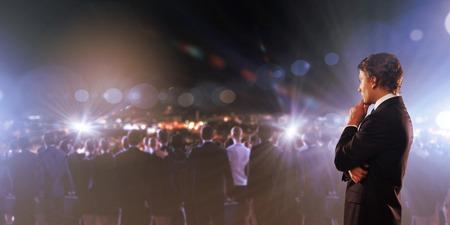 hablar en publico: Hombre de negocios pensativo joven y multitud de gente de negocios