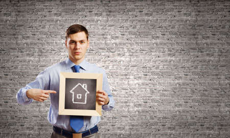 Unrecognizable businessman holding wooden frame with house sketch photo
