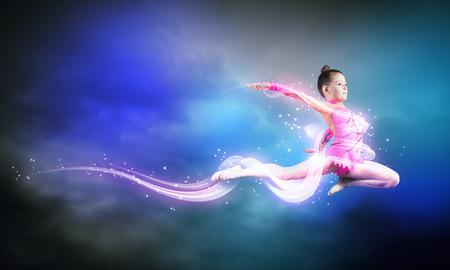 高いジャンプを作る小さなかわいい女の子体操