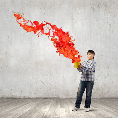 express feelings: Young boy splashing colorful paint from bucket Stock Photo