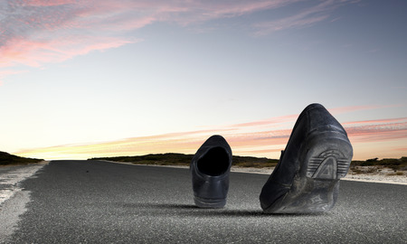 Pair of black shoes walking on road Stock Photo