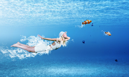 Young woman in white dress swimming under water photo