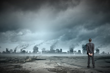 city people: Rear view of businessman looking at ruins of city Stock Photo