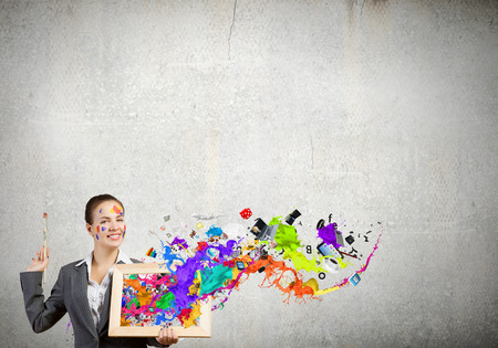 Young attractive woman in suit with paint brush in hand Stock Photo