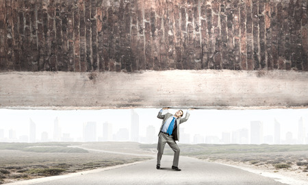man power: Young powerful businessman lifting brick wall above head