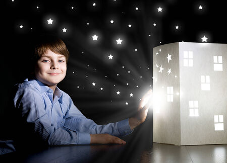 Cute little boy in dark room dreaming about home and family photo