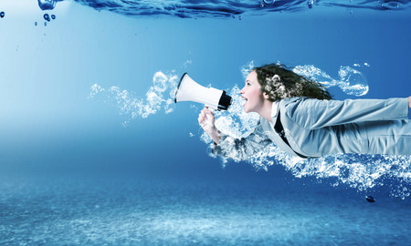 Young businesswoman in suit swimming in crystal blue water Stok Fotoğraf