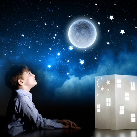 little model: Cute little boy in dark room dreaming about home and family