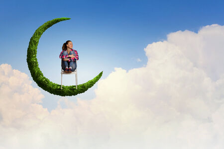 Young pretty girl sitting on moon in sky photo