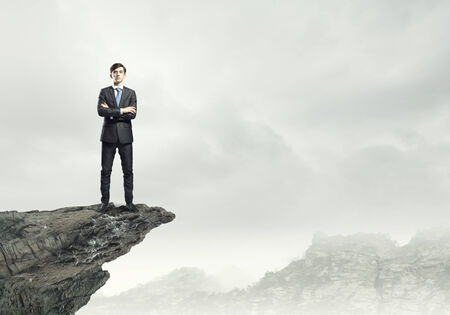 views of the mountains: Confident businessman standing on top of rock Stock Photo