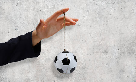 manipulate: Close up of businessman hand and ball hanging on rope