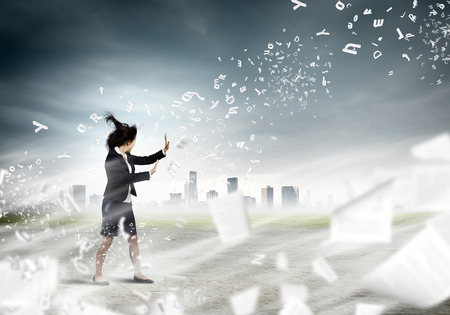 formals: Young determined businesswoman walking against strong wind Stock Photo