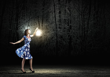 Young woman in blue dress walking in night wood photo