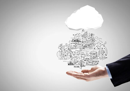 Close up of businessman hand holding cloud with business sketches Stock Photo