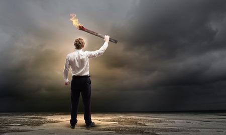 Jeune homme d'affaires exploitation brûlant torche à la main
