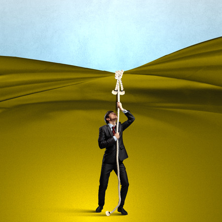 Young businessman pulling curtain with rope. Place for text photo
