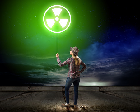 radioactivity: Young woman in casual holding balloon with radioactivity sign Stock Photo