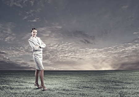 Young attractive businesswoman standing on green field photo
