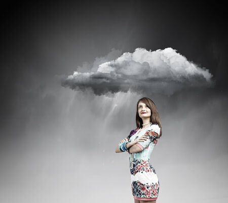Young pretty woman standing under raining cloud photo