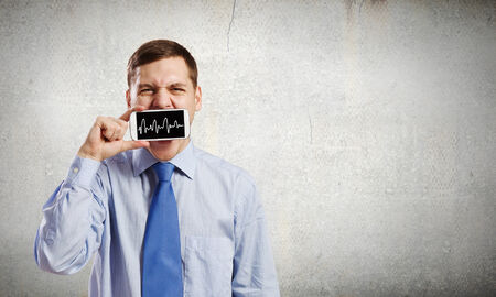 voicemail: Young handsome businessman hiding mouth behind mobile phone Stock Photo