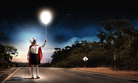 caped: Cute girl of school age in superhero costume with balloon in hand Stock Photo