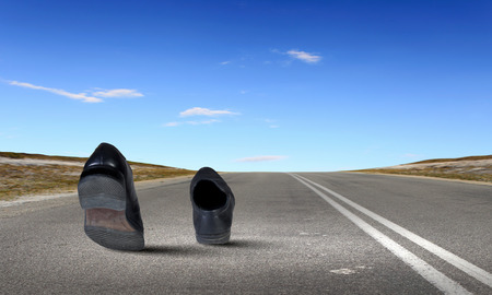 Paar zwarte schoenen die op weg lopen