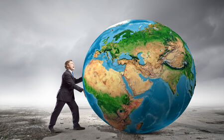 end of world: Businessman pushing big Earth planet.  Stock Photo