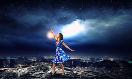 magical equipment: Young woman in blue dress with lantern
