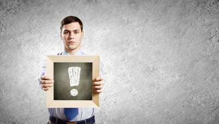determinism: Young smiling businessman holding chalkboard with exclamation sign Stock Photo
