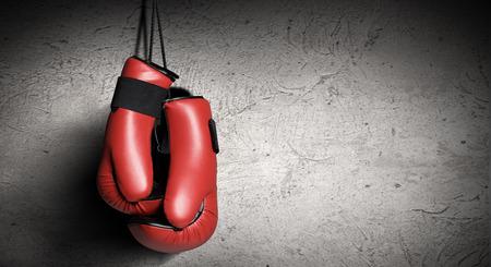 Pár červené boxerské rukavice visící na stěně