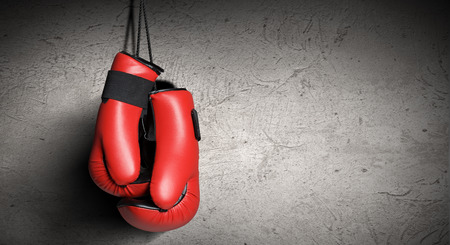 guantes de box: Un par de guantes de boxeo rojos que cuelgan en la pared