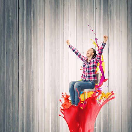 Young woman in casual with arms up celebrating success photo
