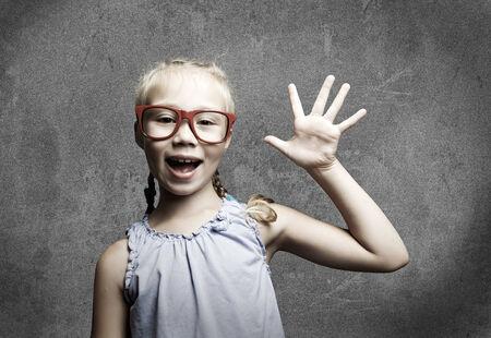 Genius girl in red glasses near blackboard with formulas photo